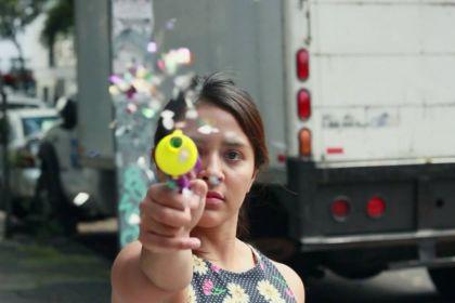 Une femme tire avec un pistolet à confettis