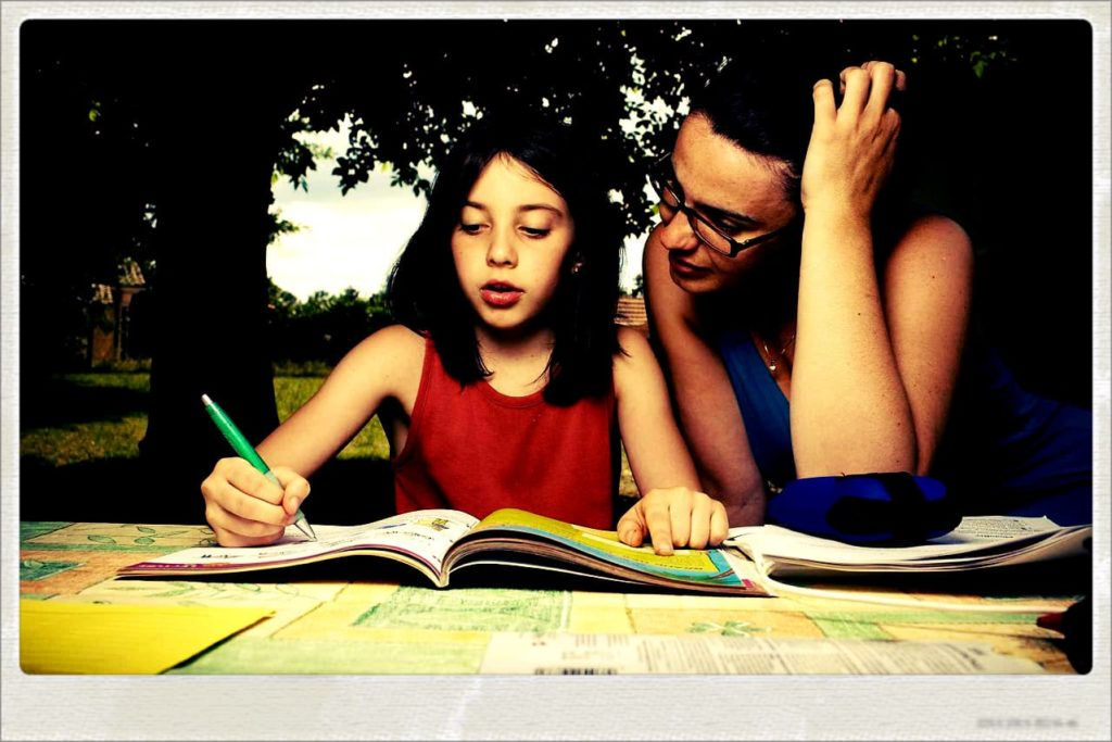 Une maman qui aide sa fille à faire son cahier de vacances