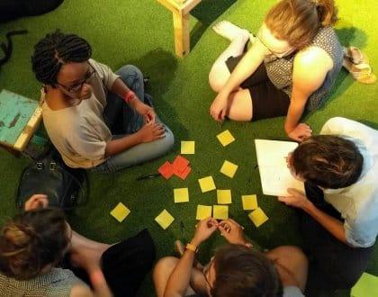 Des participants écrivent des mots-clés sur des post-it lors de la soirée ExistenZ