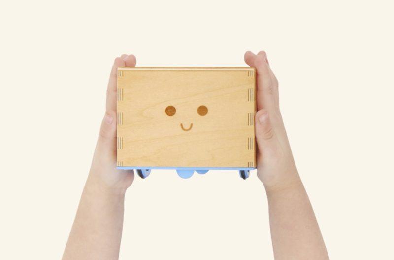 Un enfant tient Cubetto dans ses mains