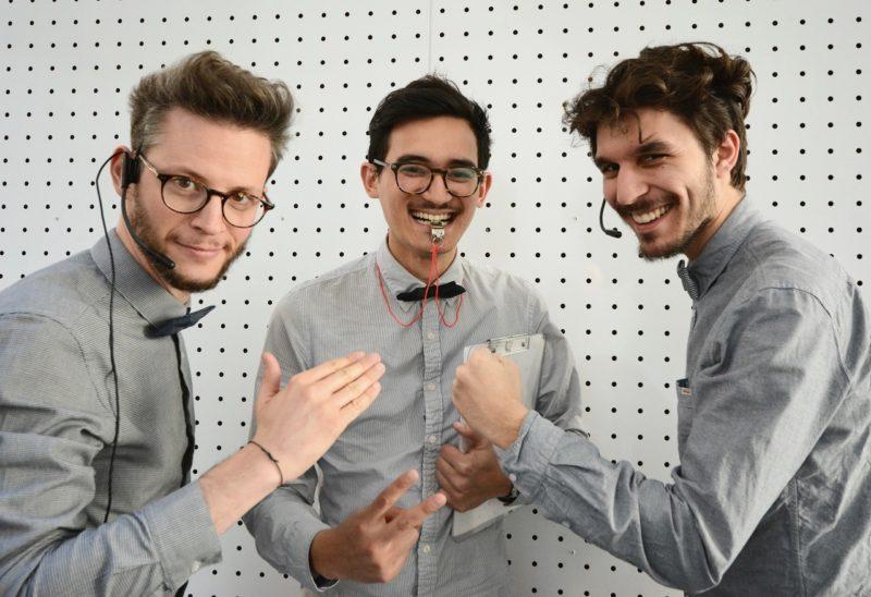 Trois hommes jouent à shifumi.